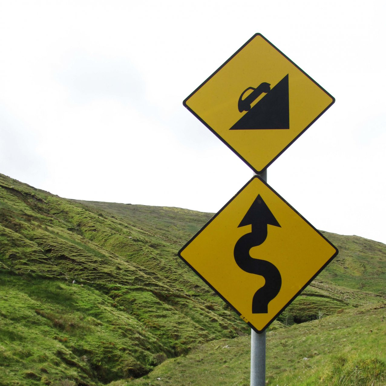 Roadsigns indicating a twisting, uphill climb ahead, with green hills in the background, somewhere in Ireland