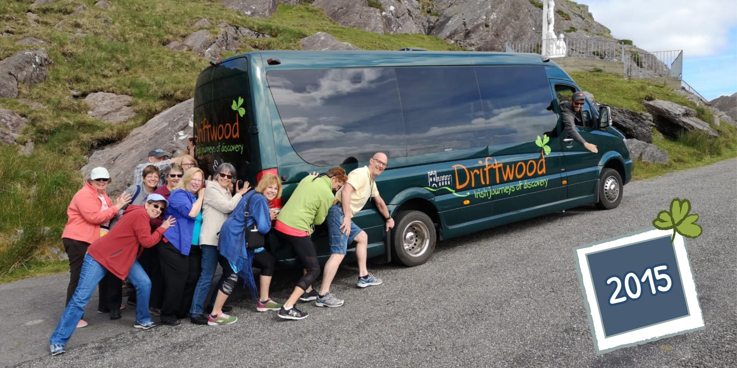 A smiling group of Driftwood tour guests pranking around with a Drifter tour vehicle and guide