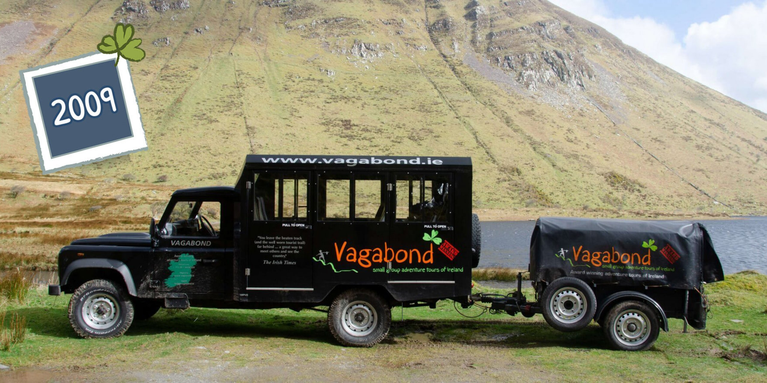 An original Land Rover Defender VagaTron tour vehicle with branded trailer parked in a scenic location in Ireland; side view