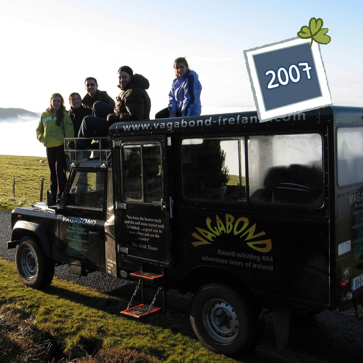 Vagabond Tours guest group sitting and standing on an original Land Rover Defender VagaTron tour vehicle with a 2007 date graphic in the top right corner