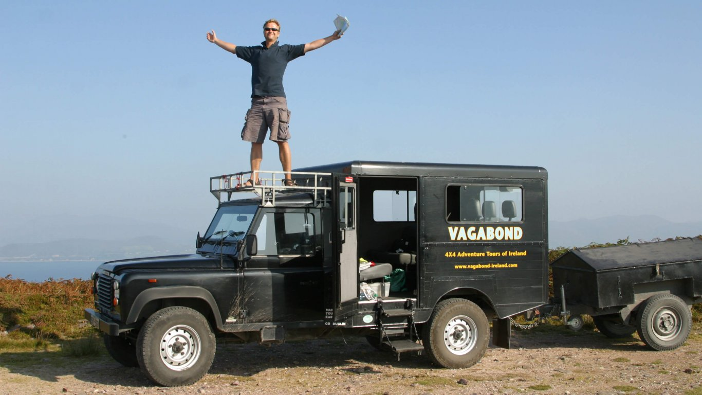 Rob Rankin standing on the cab of an old Land Rover Defender VagaTron tour vehicle against a blue sky