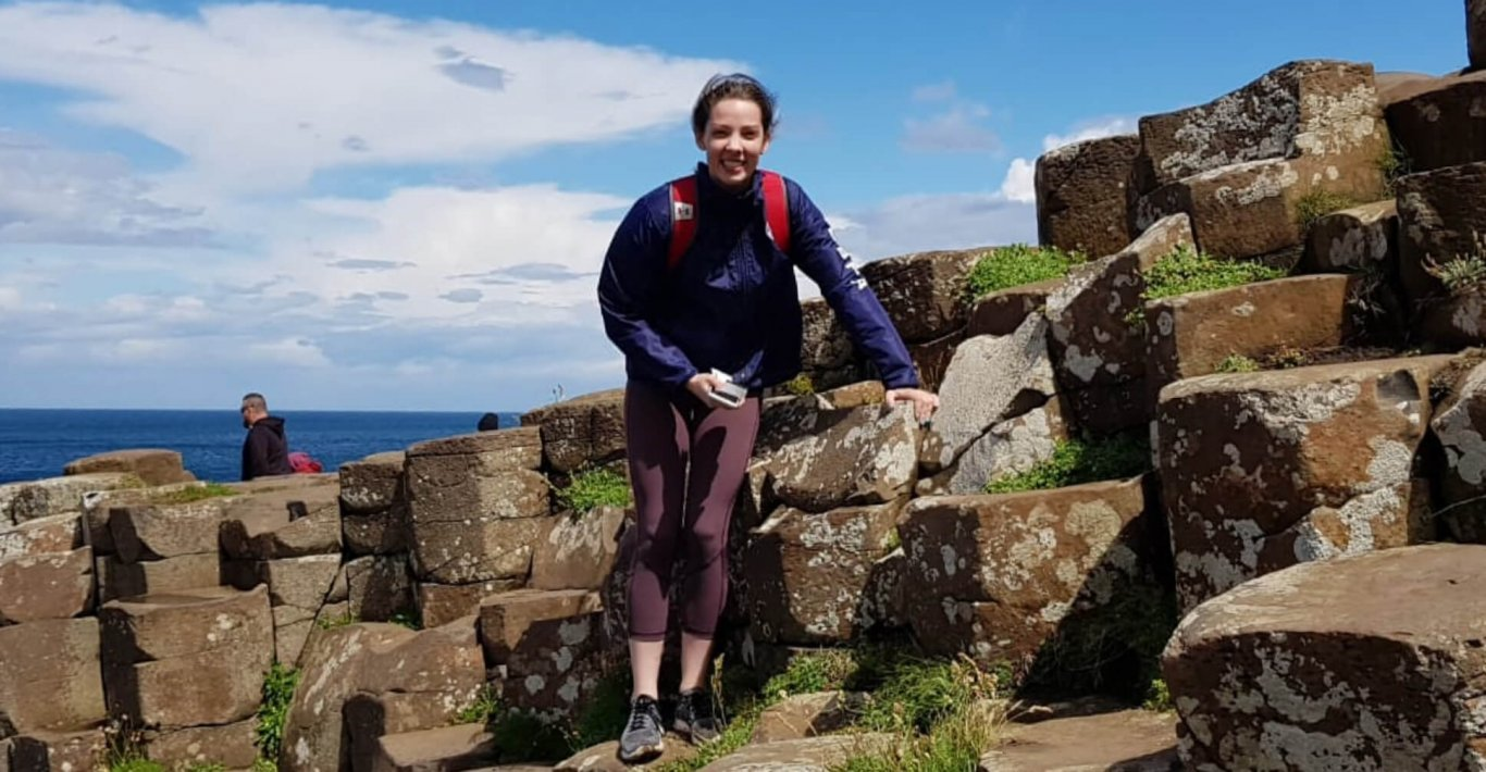 Female guest smiling at the camera while posing on the Giant's Causeway in Northern Ireland