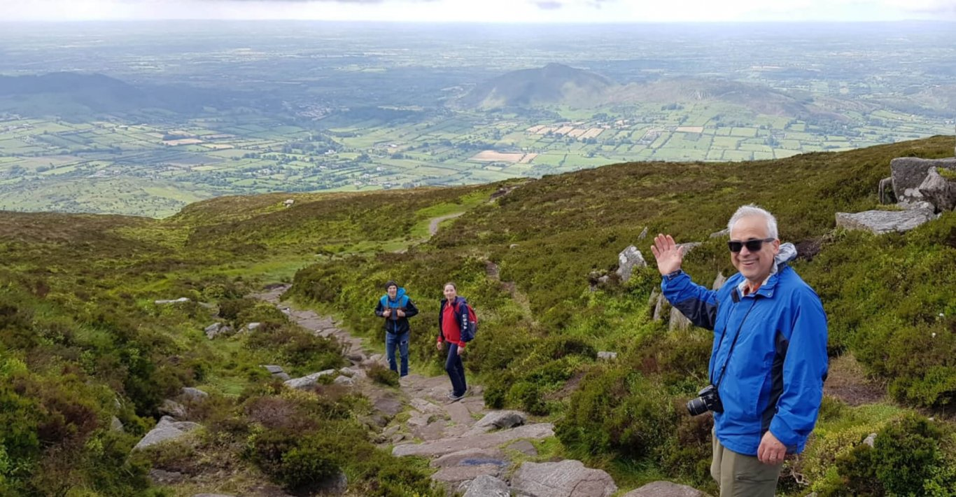 Man waving at the camera while hiking Slieve Gullion in Northern Ireland