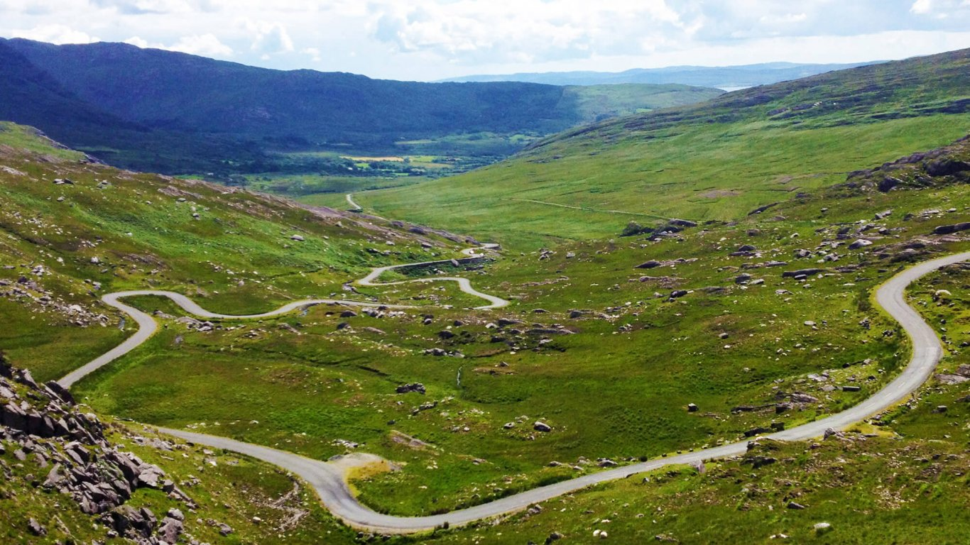 Twisting road and green mountains on the Healy Pass in Ireland