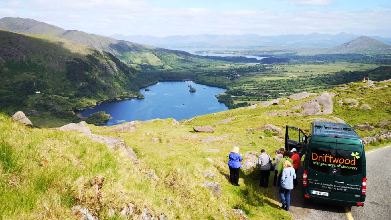 A Driftwood tour vehicle and tour group stopped at a scenic spot on the Healy Pass in Ireland