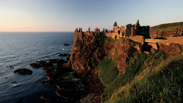 Sunset strikes the ruins of Dunluce Castle in Northern Ireland