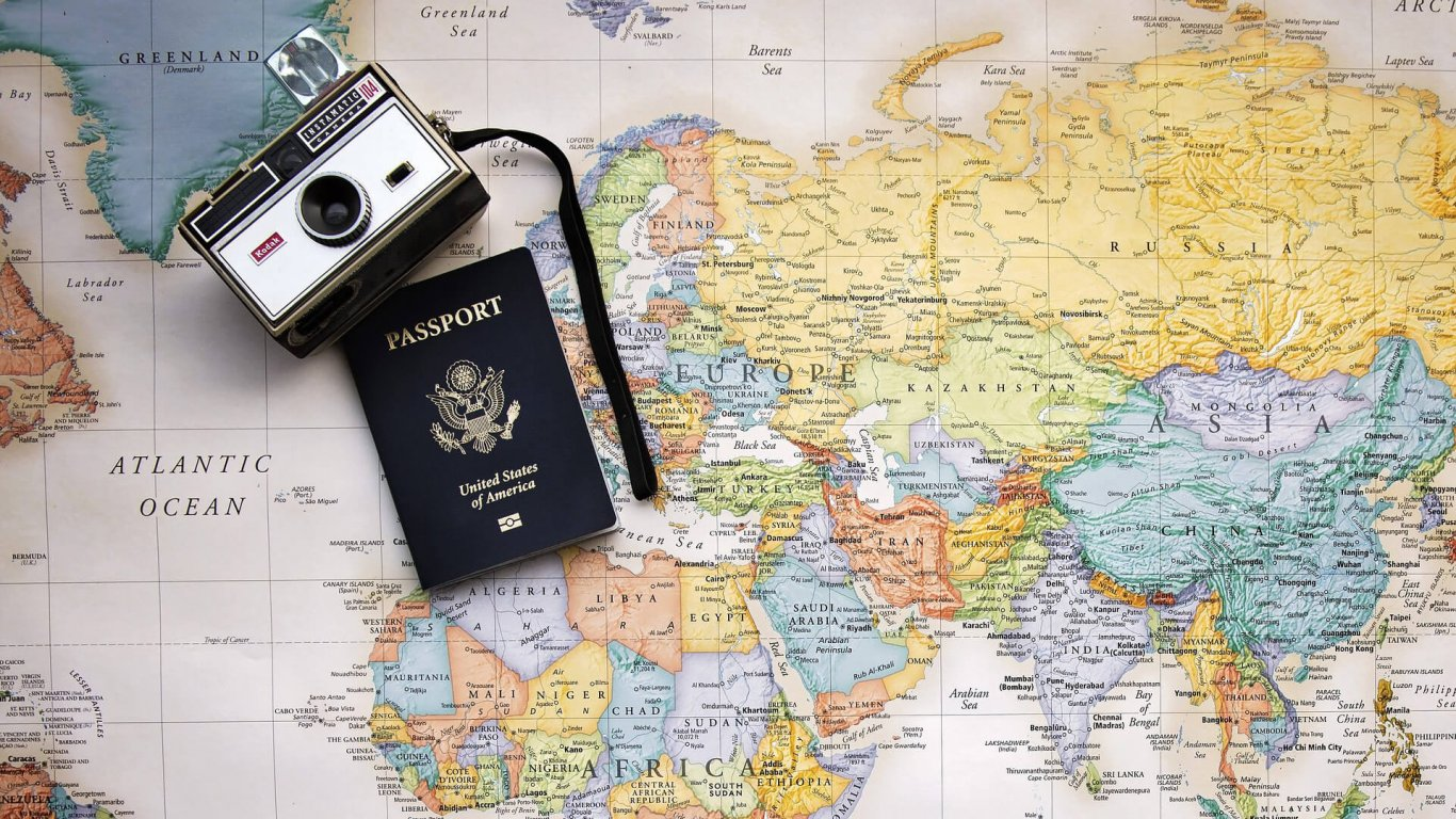 US Passport and retro camera on top of a map of the world