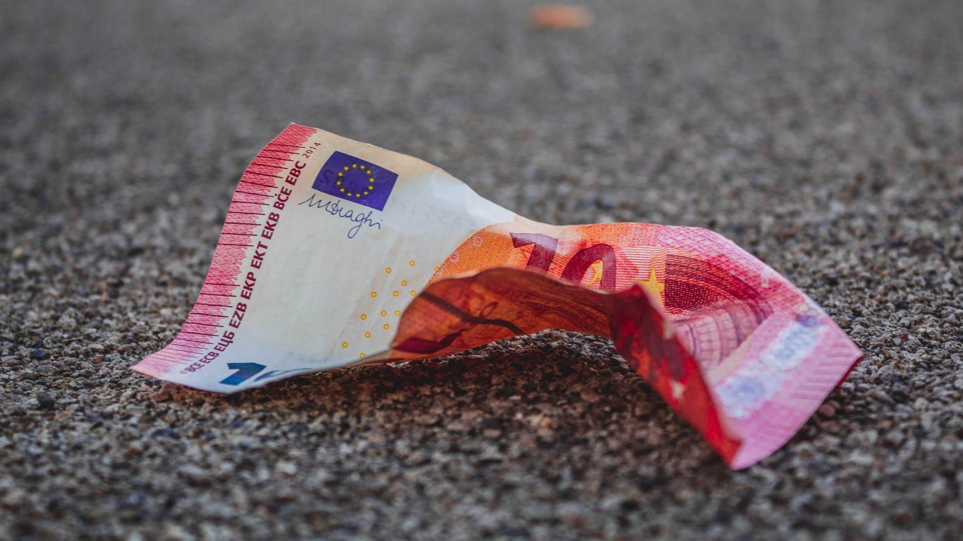 Crumpled euro note resting on tarmac