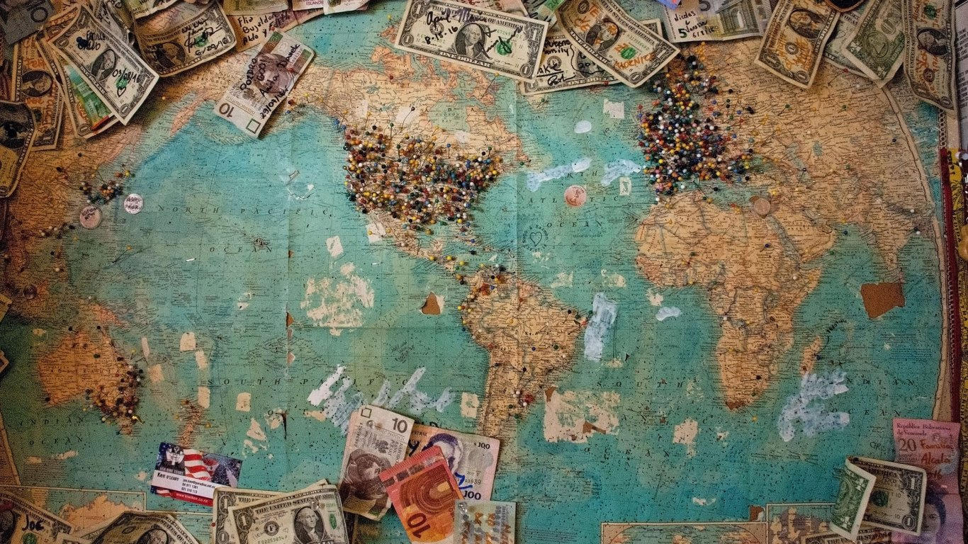 A world map with dollars and euros spread all over it and pins stuck in America and Europe