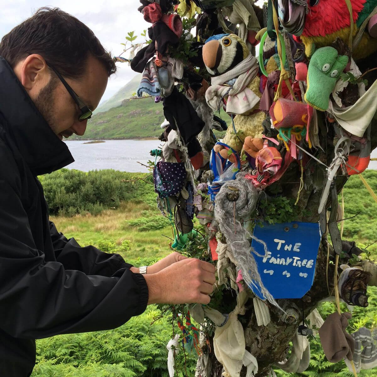 Fastening a charm to a fairy rag tree in Ireland