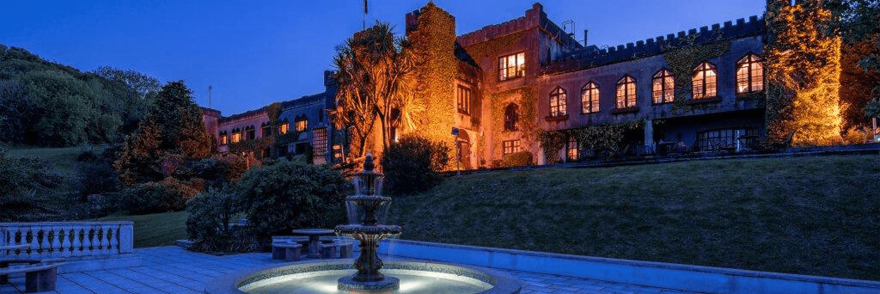 The exterior of Abbeyglen Castle at dusk with fountain in garden