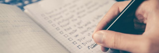 A person writing ticking off a checklist