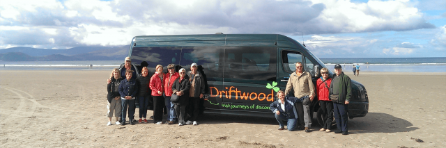 A Driftwood group standing in front of their tour bus on a beach