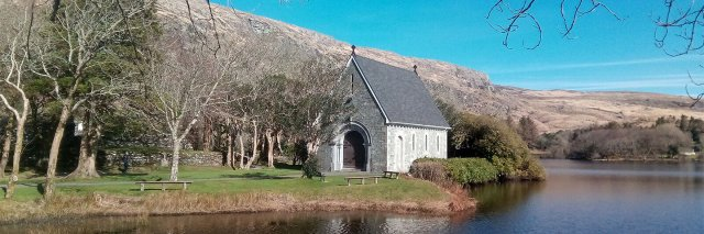 Gougane Barra church on a sunny day with the mountains in the background