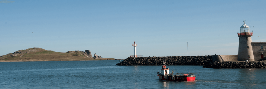 A panoramic view of Howth Harbour with an island in the distance and a lighthouse in view