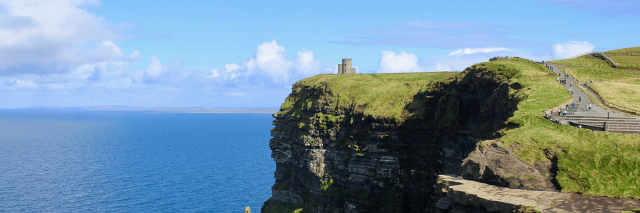 A view of the Cliffs of Moher on a sunny day with blue skies overlooking the sea