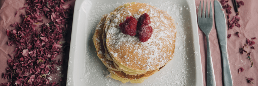 A plate of pancakes with raspberries on top surrounded by pink flowers and a knife and fork