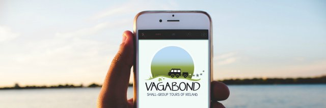 A hand holding a phone showing Vagabond logo on the screen with the sea in the background