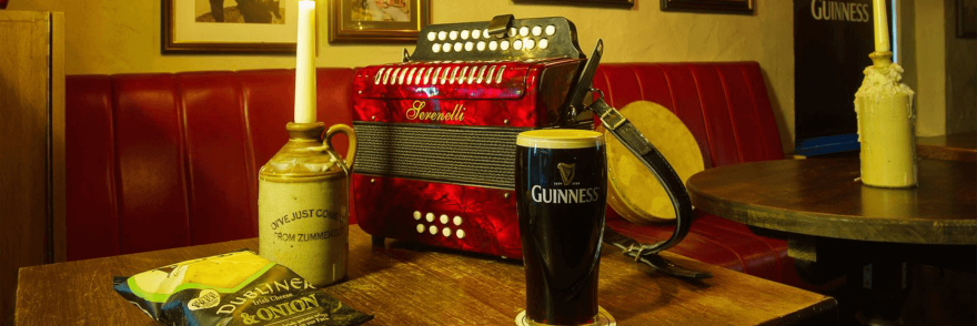 A pint of Guinness sitting on a table in an old Irish pub surrounded by a candle, crisps and an old instrument
