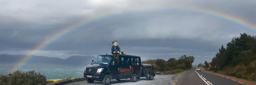 An animated small leprechaun sitting on top of a Vagabond tour vehicle under a rainbow