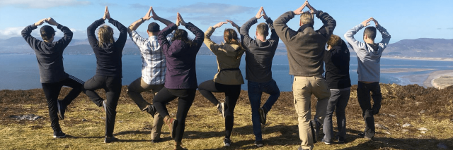 A group of Vagabonds at a viewing point overlooking Glenbeigh beach doing some yoga