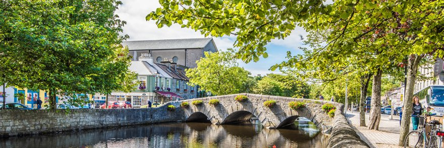 Westport Town on a sunny day with trees and a river in view
