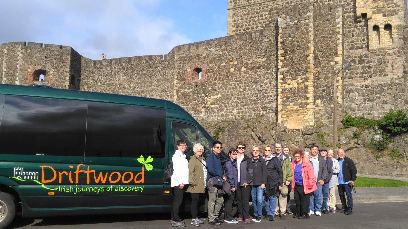 A Driftwood tour group posing in front of their mini-coach outside an Irish castle