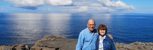 Two tour guests in front of a blue sky and ocean in Ireland