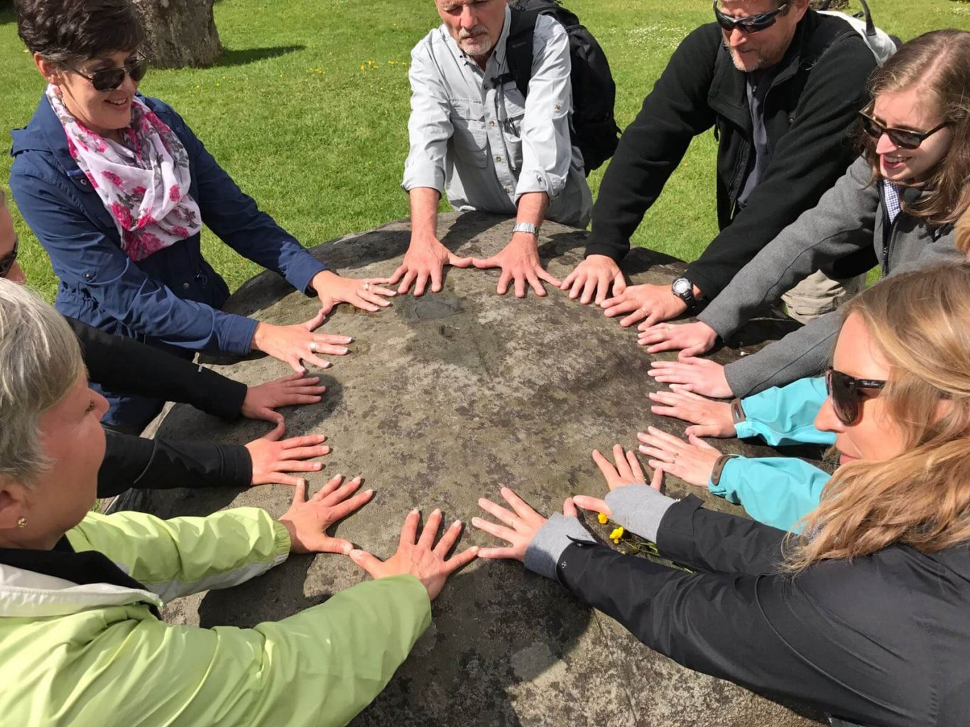 Driftwood tour group place their hands on an ancient stone