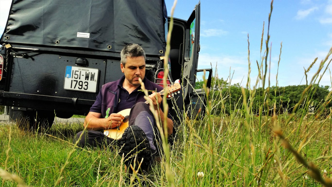 VagaGuide Tour Guide Tim playing his mandolin on tour beside his Vagabond tour vehicle in Ireland