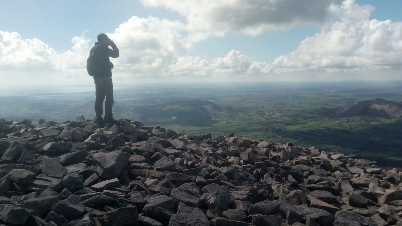 A man standing on the summit of Slieve Gullion looking down over the landscape