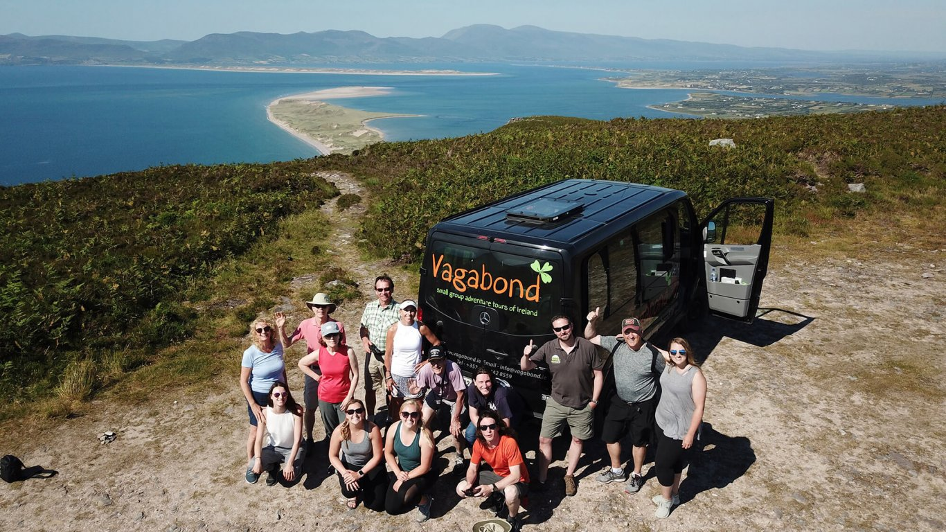 Vagabond tour group posing beside tour vehicle at scenic spot on Ring of Kerry in Ireland