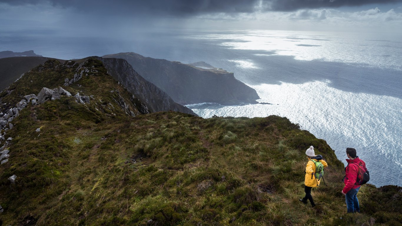 A couple hiking along the Slieve League cliffs with a magnificent view of the Atlantic Ocean