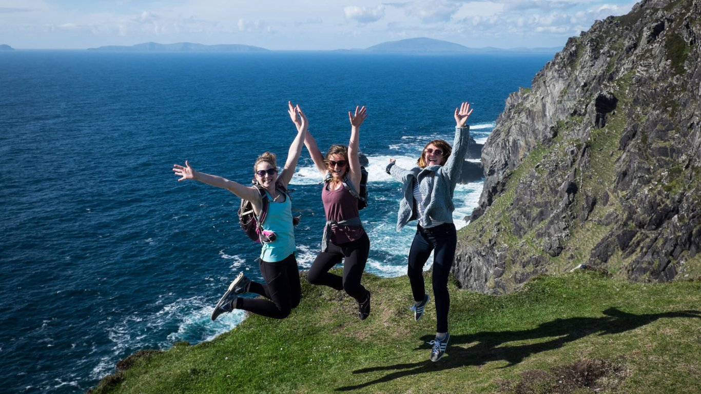 Three Vagabond women jumping for joy with their arms in the air overlooking Bray Head