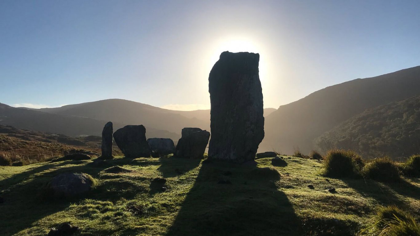 A silhouette of the Uragh stone circle as the sun beams behind it