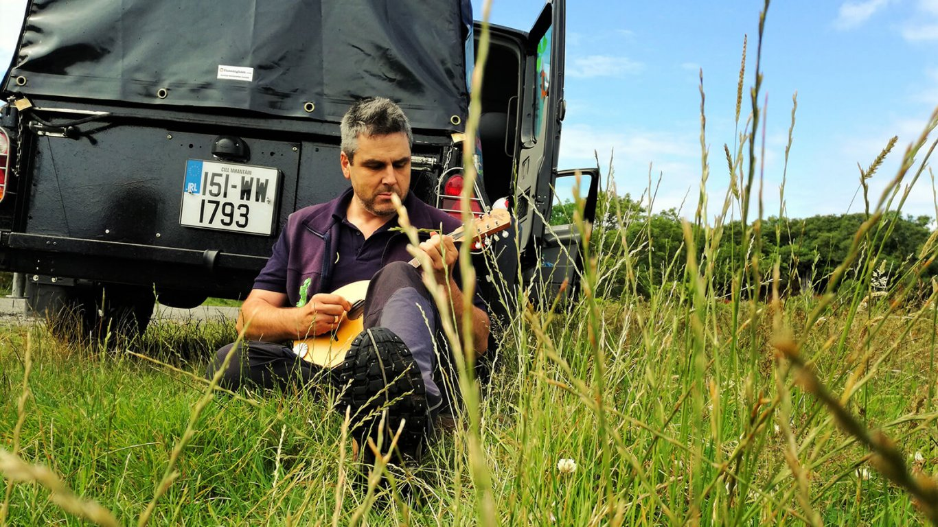VagaGuide Tim relaxes beside tour vehicle while playing music in Ireland