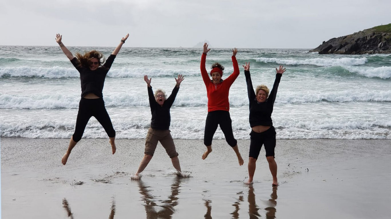 Four Vagabond Tours guests jump for joy on the beach in Ireland