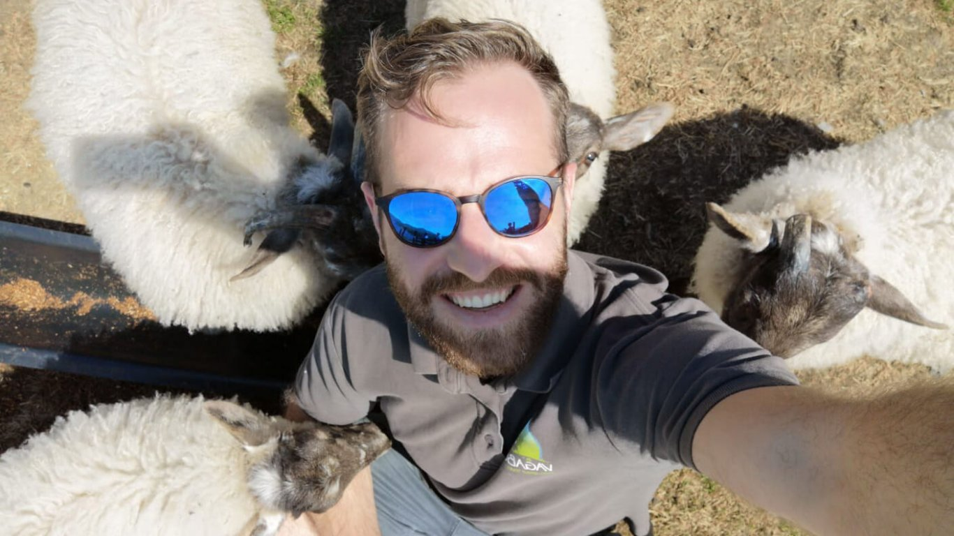 VagaGuide Sean snaps a selfie of himself with some lambs in Ireland