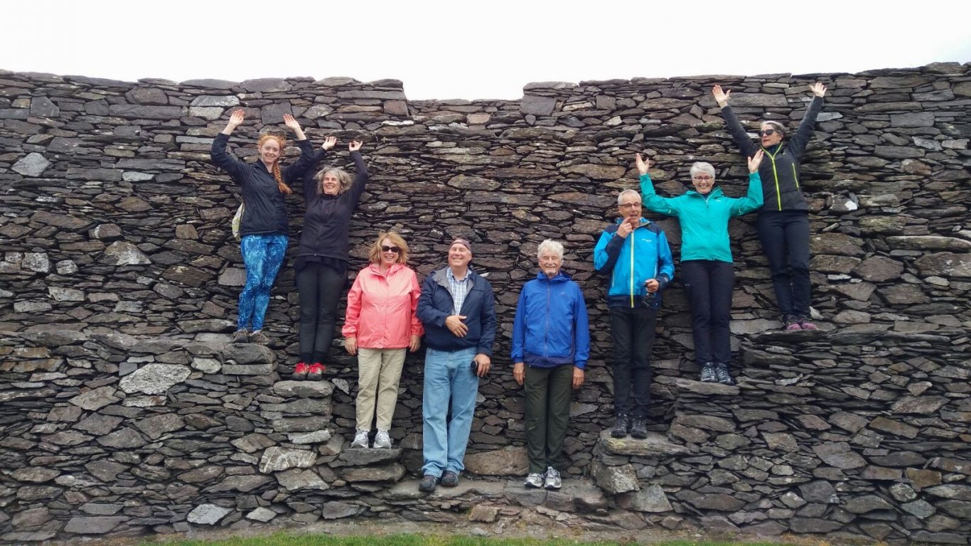 Group of Vagabond tour passengers posing on Cahergal stone fort walls