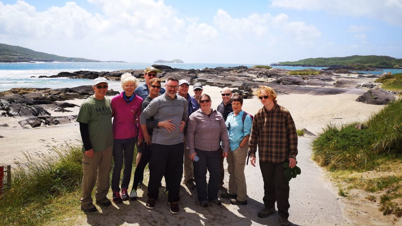 Vagabond tour group posing in the sunshine at Derrynane beach in Ireland