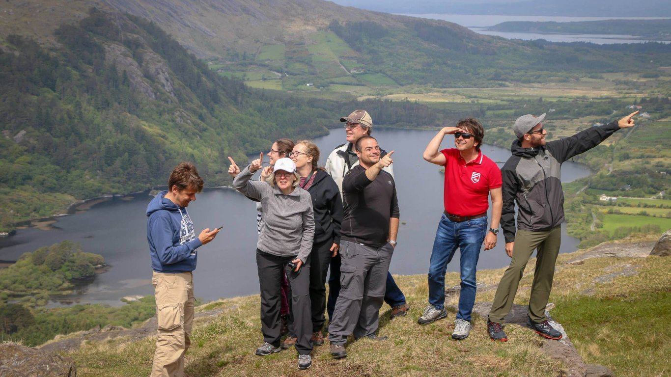A group of Vagabond tour guests smile and point in different directions at Ladies View in Ireland