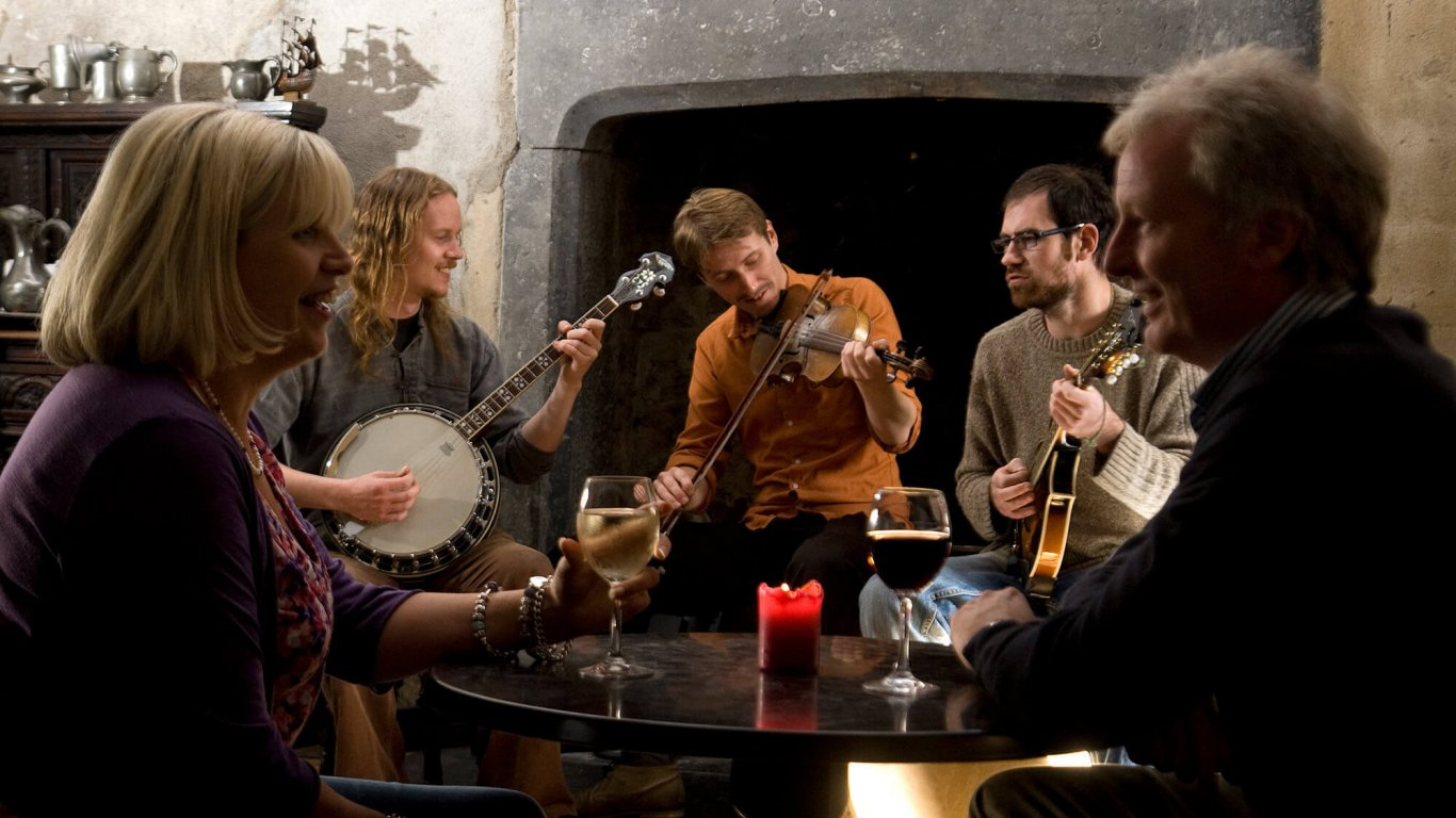 A middle-aged couple face each other over a table while three younger traditional Irish musicians play in the background