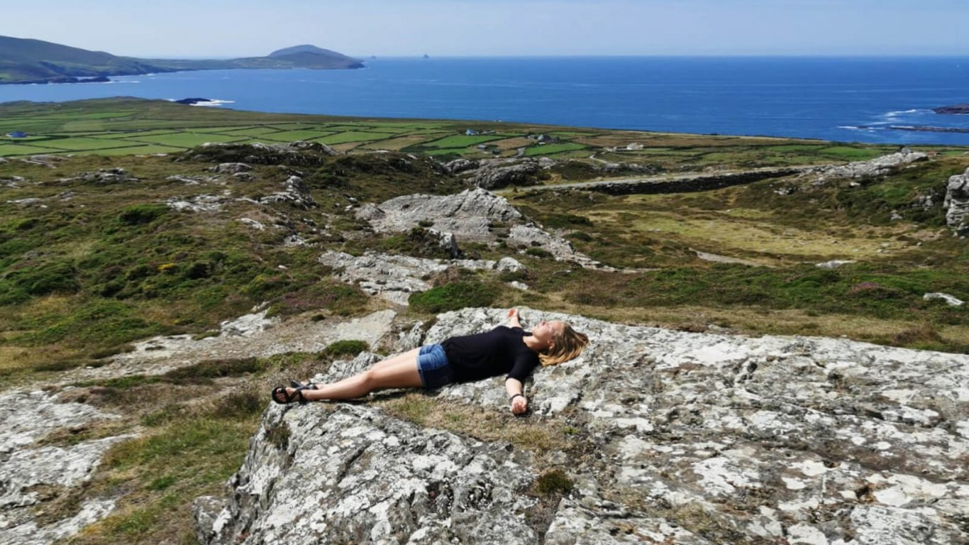 Female Vagabond tour guest lying in a scenic landscape in Ireland looking serene