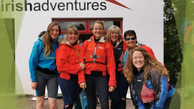 Female tour guests with Vagabond tour guide smiling at a kayaking centre