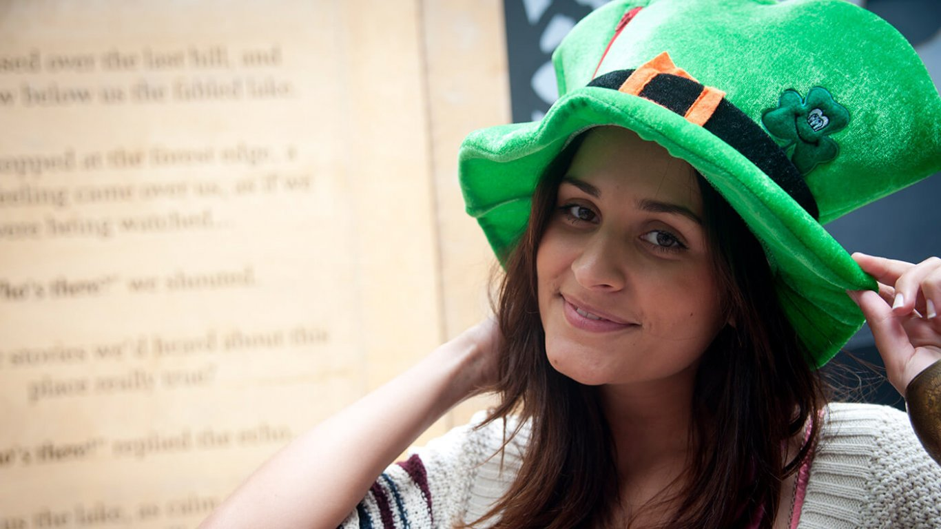 A girl wearing a green leprechaun top hat