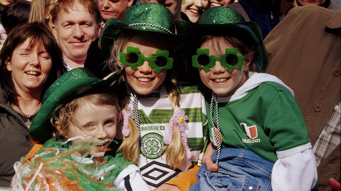 Three kids dressed up in green jerseys and clothes and glasses at a st patricks day parade
