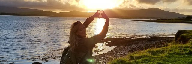 Female tour guest with sunset during summer in Ireland