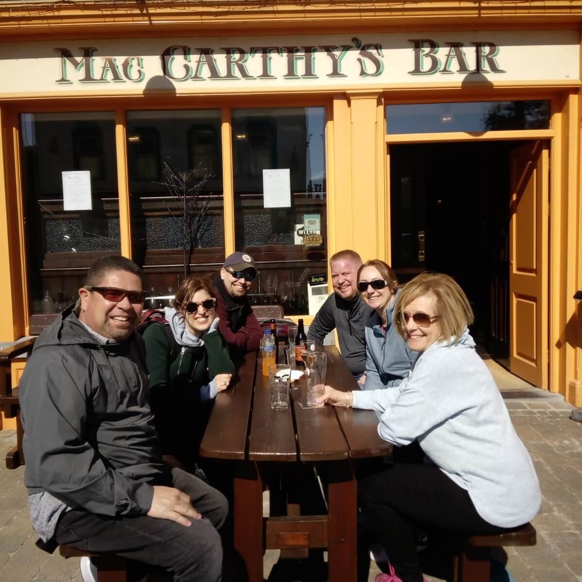 Happy tour group sitting outside McCarthy's pub during summer in Ireland