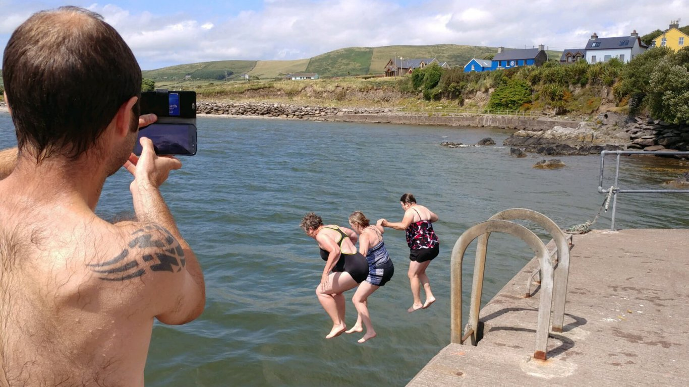 Three ladies jumping off a pier into the sea during summer in Ireland