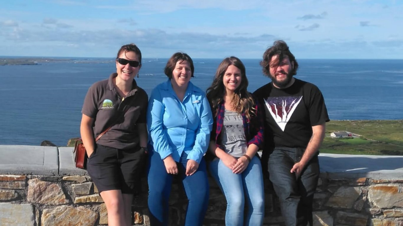 VagaGuide tour guide Bebhinn with three smiling guests in a scenic location in Ireland